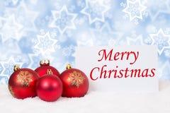Desejos vermelhos do cartão da neve do inverno das bolas do Feliz Natal Foto de Stock