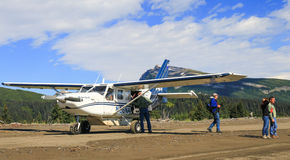 Desembarco por playa del avión de Alaska Bush con la gente Foto de archivo libre de regalías