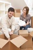 Desempaque de los pares o cajas de embalaje que mueven la casa Imágenes de archivo libres de regalías