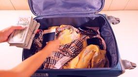 Desempaquetando la maleta por completo de ropa del dinero y del verano metrajes