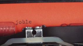 Desempregado - datilografado em uma máquina de escrever velha do vintage Impresso no papel vermelho O papel vermelho é introduzid filme