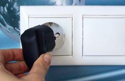 Desenchufe o enchufó el concepto, mano que sostiene el enchufe eléctrico imagen de archivo libre de regalías