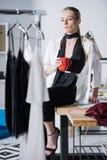 desenhador de moda atrativo novo que senta-se na mesa do trabalho com xícara de café e vista imagens de stock