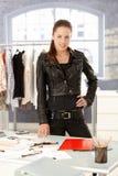 Desenhador de moda atrativo que está pela mesa fotografia de stock
