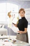 Desenhador de moda atrativo que trabalha na mesa foto de stock