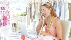 Desenhador de moda atrativo que trabalha no portátil e que responde ao telefone filme
