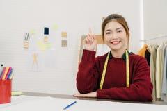 Desenhador de moda fêmea asiático bonito profissional que trabalha com esboços da tela e projeto de tiragem da roupa no estúdio fotografia de stock