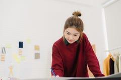 Desenhador de moda fêmea asiático que trabalha com esboços da tela e projeto de tiragem da roupa no estúdio foto de stock royalty free