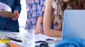 Desenhador de moda fêmea atrativo novo que trabalha na mesa de escritório, desenhando ao falar no móbil imagens de stock