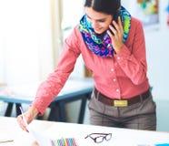 Desenhador de moda fêmea atrativo novo que trabalha na mesa de escritório, desenhando ao falar no móbil fotografia de stock royalty free