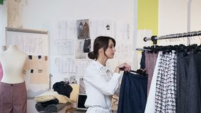 Desenhador de moda fêmea atrativo que toma calças da cremalheira da roupa com roupa à moda elegante vídeos de arquivo