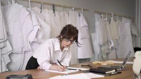 Desenhador de moda fêmea que faz as anotações que inclinam-se na tabela filme