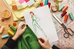 Desenhador de moda fêmea que trabalha com amostra da tela e ilustração tirada imagens de stock