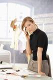 Desenhador de moda novo que fala no móbil foto de stock