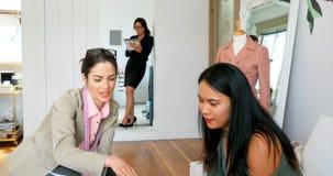 Desenhador de moda que discute o esboço com um cliente fêmea 4k vídeos de arquivo