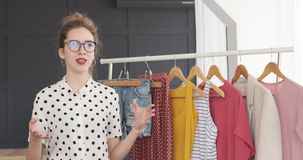 Desenhador de moda que fala sobre a coleção nova do vestido no boutique vídeos de arquivo