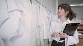 Desenhador de moda que faz anota??es ao olhar testes padr?es em costurar o est?dio vídeos de arquivo