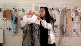 Desenhador de moda que fixa a roupa no manequim video estoque