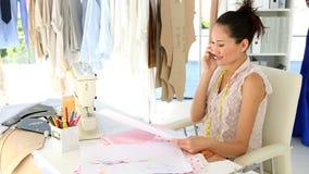 Desenhador de moda que senta-se na tabela que fala no telefone vídeos de arquivo