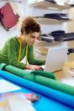 Desenhador de moda que trabalha com portátil fotografia de stock