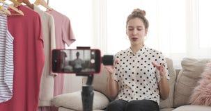 Desenhador de moda que usa o telefone celular para o equipamento novo que vlogging video estoque