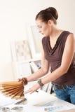 Desenhador fêmea novo com swatches de madeira da cor Imagens de Stock
