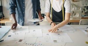 Desenhadores de moda dos povos que põem esboços sobre a tabela que aponta em drowings filme