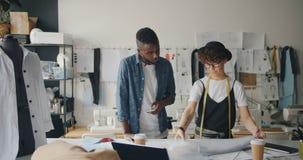 Desenhadores de moda homem e mulher que trabalham com tela e que usam o smartphone filme