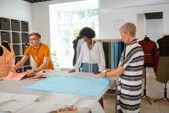 Desenhadores de moda modernos motivados que preparam-se para cortar a tela fotografia de stock
