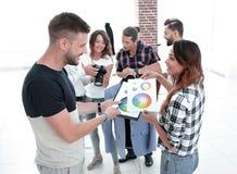 Desenhadores de moda que discutem a paleta de cores no estúdio imagem de stock