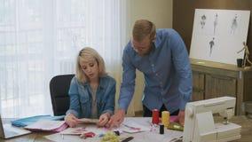 Desenhadores de moda que escolhem a paleta de cores para o projeto novo do vestido vídeos de arquivo