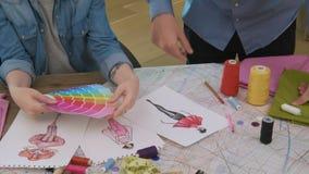 Desenhadores de moda que escolhem a paleta de cores para o projeto novo do vestido filme