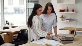Desenhadores de moda que examinam t-shirt em sua oficina video estoque