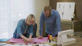 Desenhadores de moda que seguem a tela que faz o teste padrão para a roupa nova vídeos de arquivo