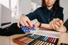 Desenhadores de moda que trabalham com amostras da tela fotos de stock