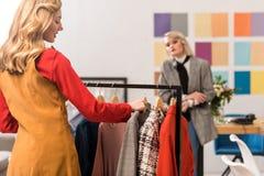 desenhadores de moda que trabalham com roupa em moderno imagem de stock