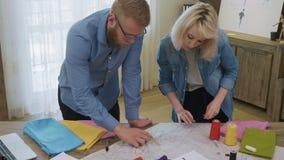 Desenhadores de moda que trabalham em um teste padrão da costura filme