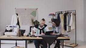 Desenhadores de moda que trabalham no escritório com as ferramentas e roupa de costura diferentes Dois desenhadores de moda homem filme