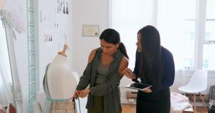 Desenhadores de moda que usam a tabuleta quando os fabricantes de medição do vestido modelarem 4k filme
