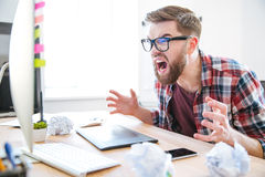 Desenhista agressivo louco do homem que olha no monitor e na gritaria Fotografia de Stock Royalty Free