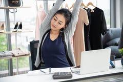Desenhista criativo asiático que estica os braços e o olho próximo na frente do laptop na mesa do trabalho foto de stock royalty free
