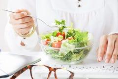 Desenhista criativo da jovem mulher que come uma salada ao trabalhar no escritório. foto de stock royalty free