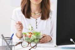 Desenhista criativo da jovem mulher que come uma salada no escritório. foto de stock royalty free