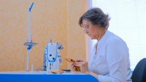 Desenhista da mulher que costura a roupa com a máquina de costura na oficina fotos de stock royalty free