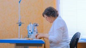 Desenhista da mulher que costura a roupa com a máquina de costura na oficina imagens de stock