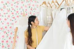 Desenhista da mulher que faz o ajuste no estúdio da forma, noiva asiática que tenta no vestido de casamento fotos de stock