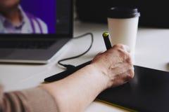 Desenhista da mulher que trabalha em um portátil com uma tabuleta de gráficos imagens de stock