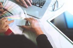 Desenhista da Web de dois colegas que discute os dados e a tabuleta digital fotos de stock