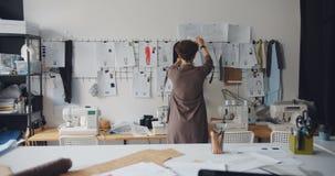 Desenhista de roupa fêmea que olha desenhos dos vestuários que penduram na parede vídeos de arquivo