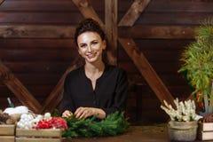 Desenhista de sorriso bonito novo da mulher que prepara a grinalda sempre-verde da árvore do Natal Fabricante da decoração do Nat fotos de stock